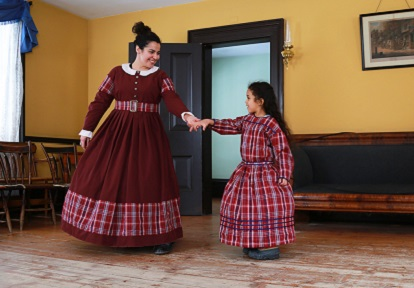 a woman and a young girl model pioneer dresses at a Black Creek Pioneer Village Discovery Station