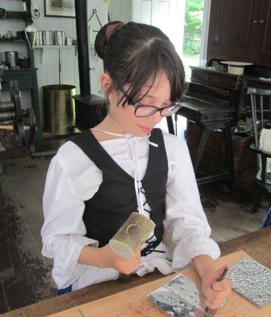 Girl practices tinsmithing at Black Creek Pioneer Village Guides and Scouts Day