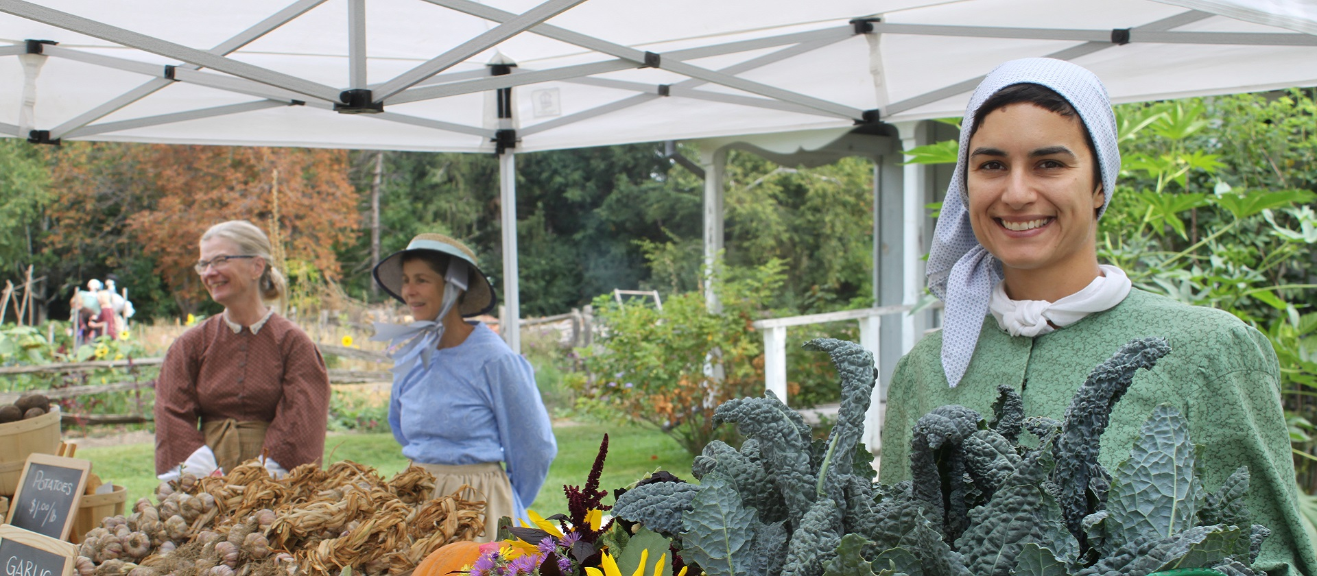 woman in pioneer costume sells fresh vegetables at the Black Creek Harvest Festival