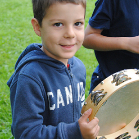 Boy plays tambourine at Black Creek Pioneer Village Guide and Scout day