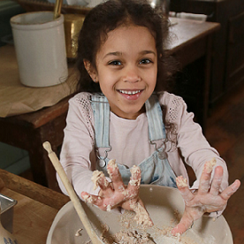 Girl learns baking at Black Creek Pioneer Village Guide and Scout Day