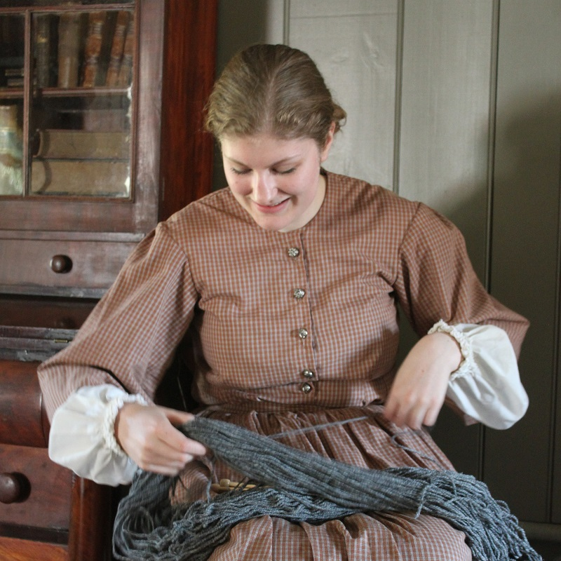 history actor in traditional dress works with yarn at Black Creek Pioneer Village