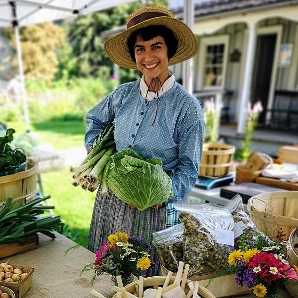 vendor in historic costume displays fresh vegetables at Black Creek Harvest Festival