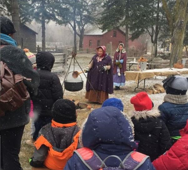 A crowd watching a pioneer women boil tree sap