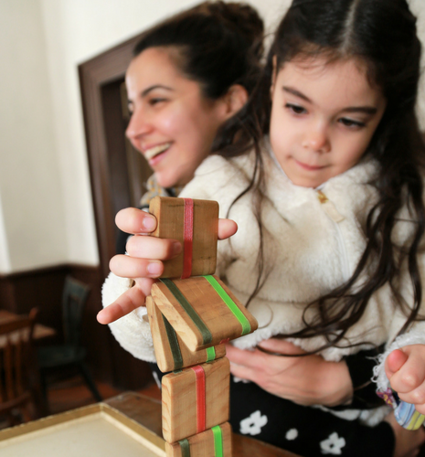 Young girl plays with a Jacobs Ladder wooden toy while being held by a woman