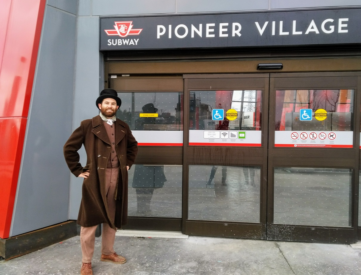 A pioneer man stands in front of the TTC Pioneer Village subway station