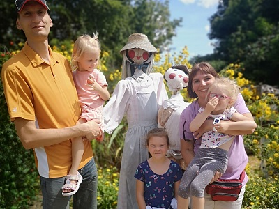 family with scarecrow at Black Creek Village fall fair