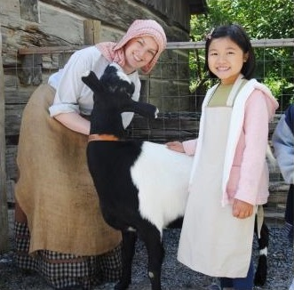 young girl meets heritage animals at Black Creek Village summer day camp
