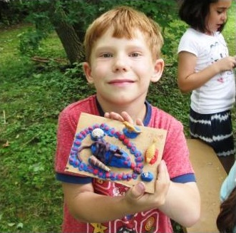 young boy makes crafts at Black Creek Village summer day camp