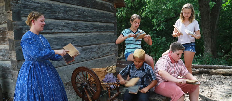 Black Creek heritage interpreter in period costume demonstrates carding wool for students