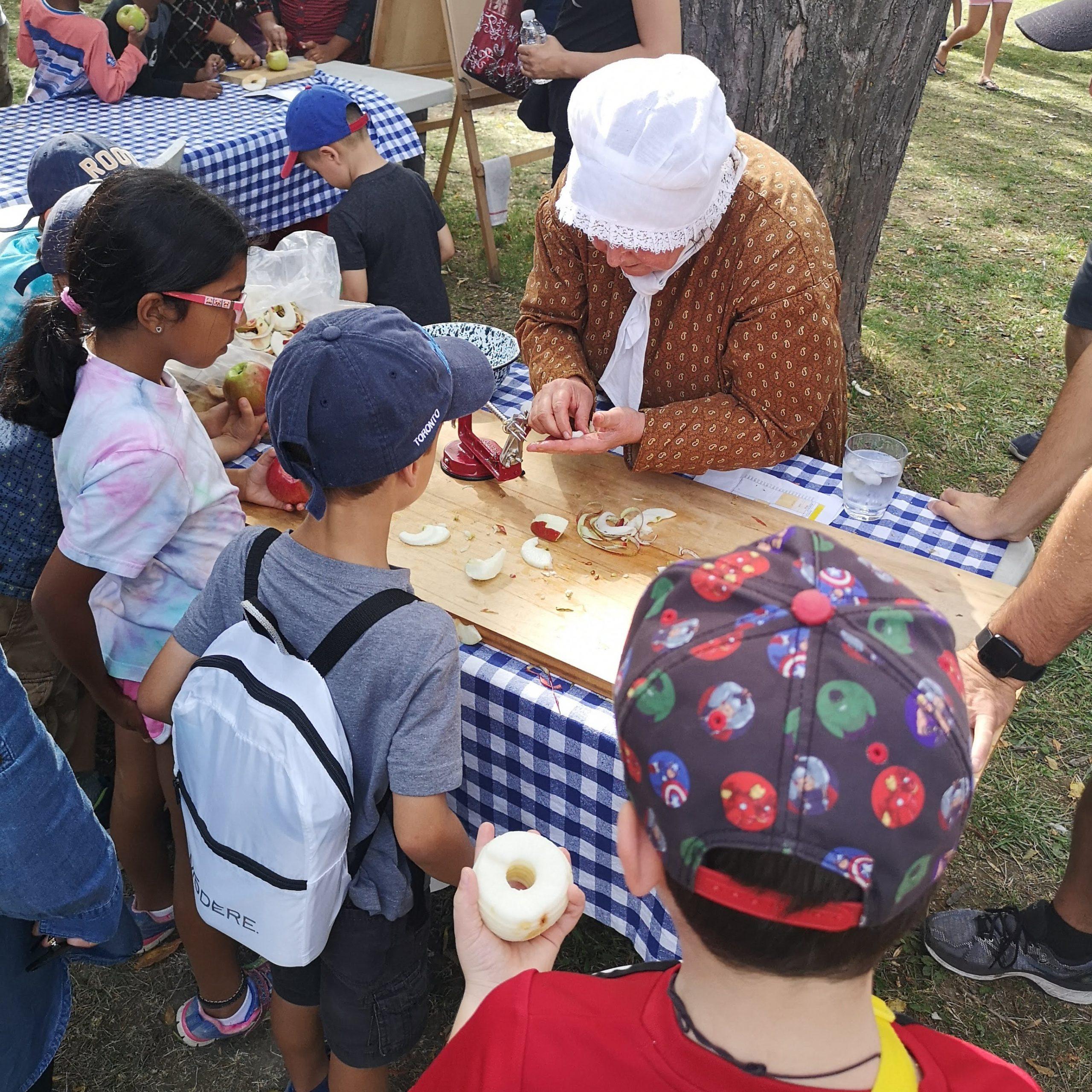 Kids and a women slicing an apple