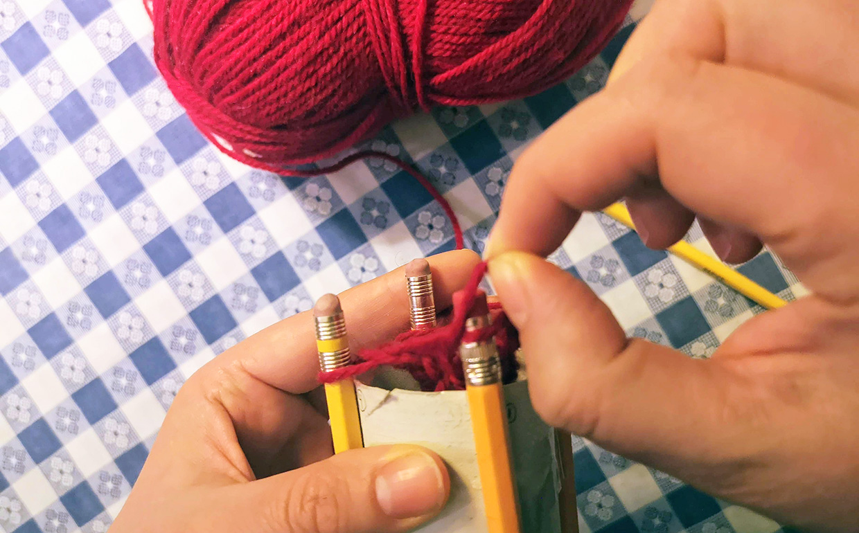 crafter casts on by passing bottom loop of yarn over top loop