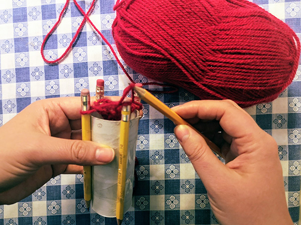 crafter wraps yarn around outside of pegs