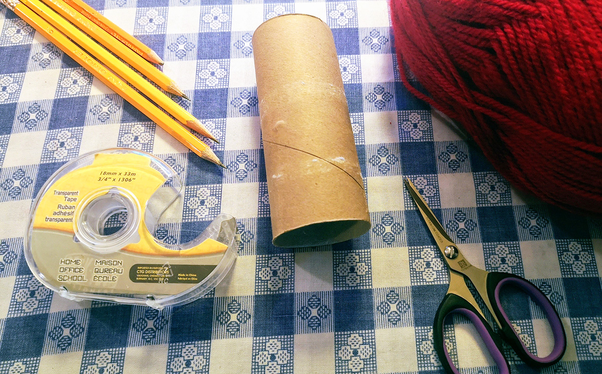 toilet paper roll with yarn and other supplies for corking tutorial
