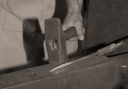 blacksmith works with hammer and anvil
