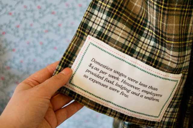 A label sewn into a garment in the Girls Bedroom portion of the Flynn House exhibit tells part of the story of women in the 19th century