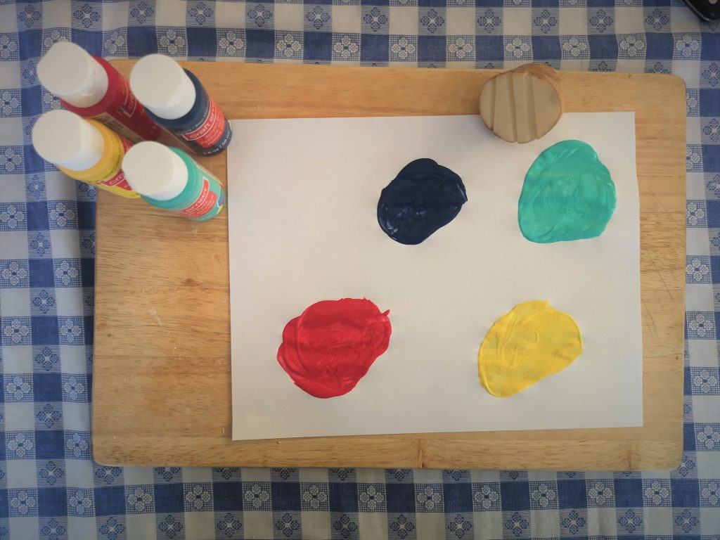 A sheet of paper with four circles of paint next to four bottles of paint