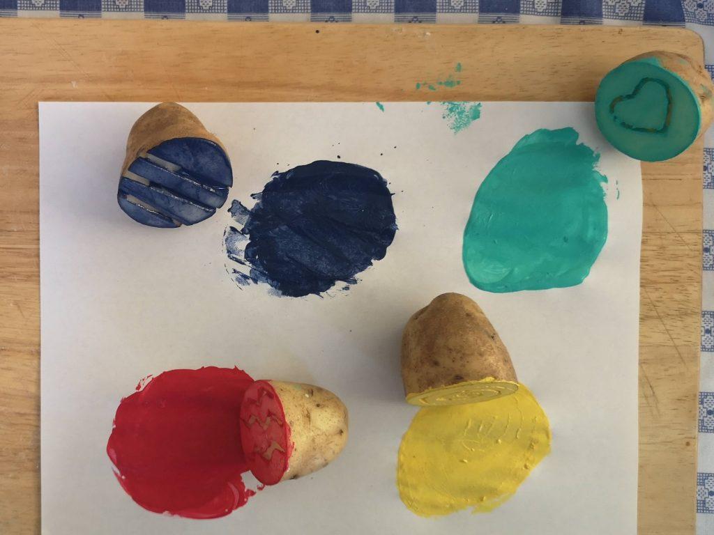 Four potato stamps next to circles of paint