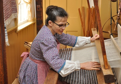 a weaver works on a loom