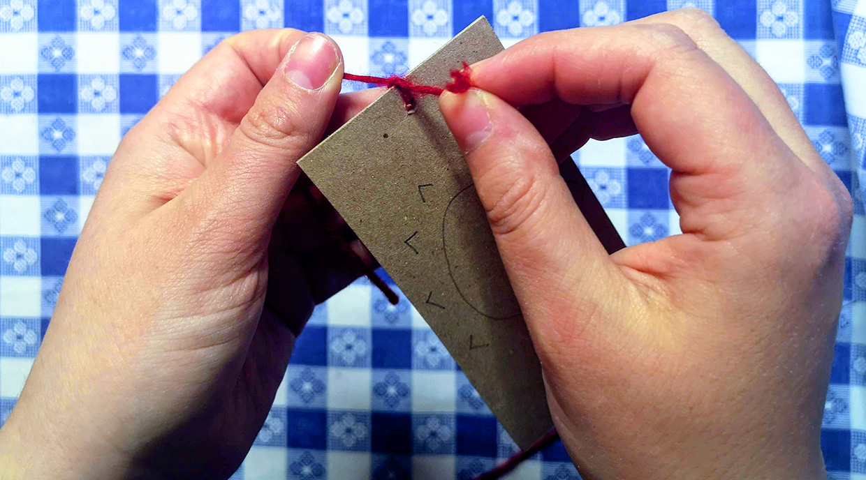 crafter threads string through hole in piece of cardboard to make an optical toy
