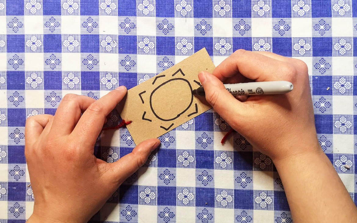 crafter draws picture of the sun on other side of piece of cardboard to make an optical toy