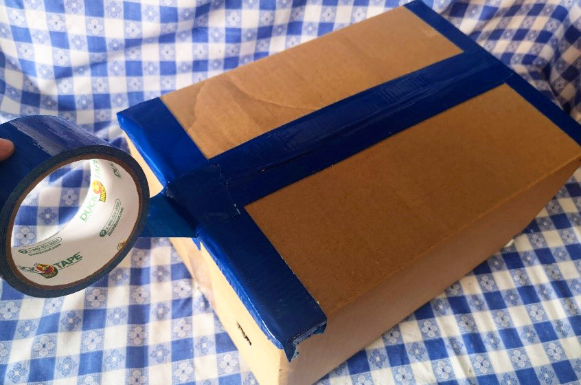 crafter uses heavy-duty tape to seal cardboard box and prevent light from leaking into camera obscura