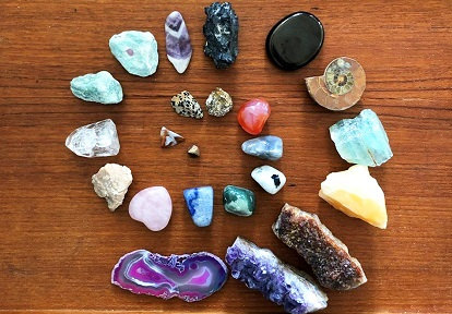 a collection of unusual rocks organized by size on a wooden tray