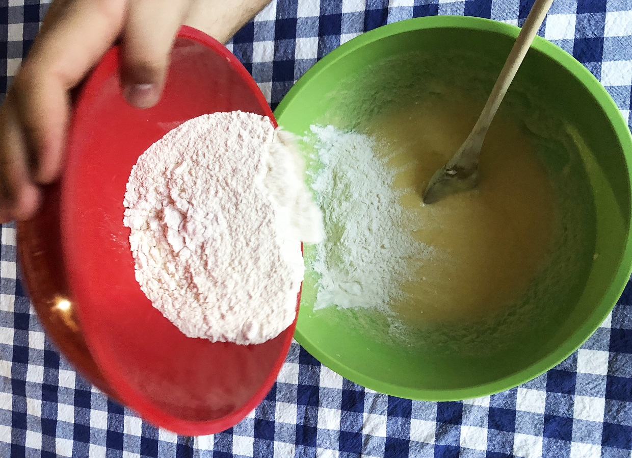 baker adds flour to cup cake mix