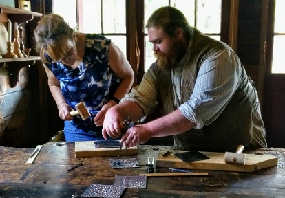 woman learns tinsmithing skills from instructor in DIY Heritage Trades workshop at Black Creek Pioneer Village