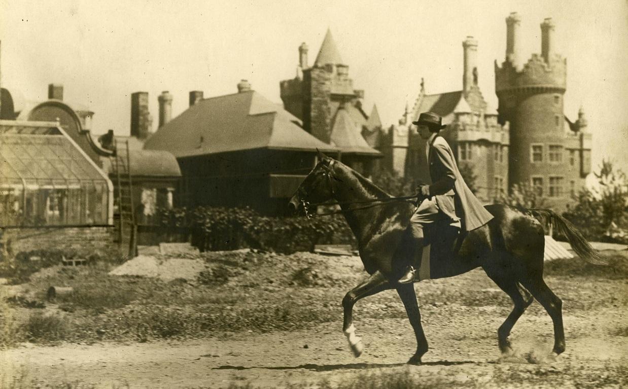 1920s photograph of woman wearing jodhpurs as she rides horseback near Casa Loma in Toronto