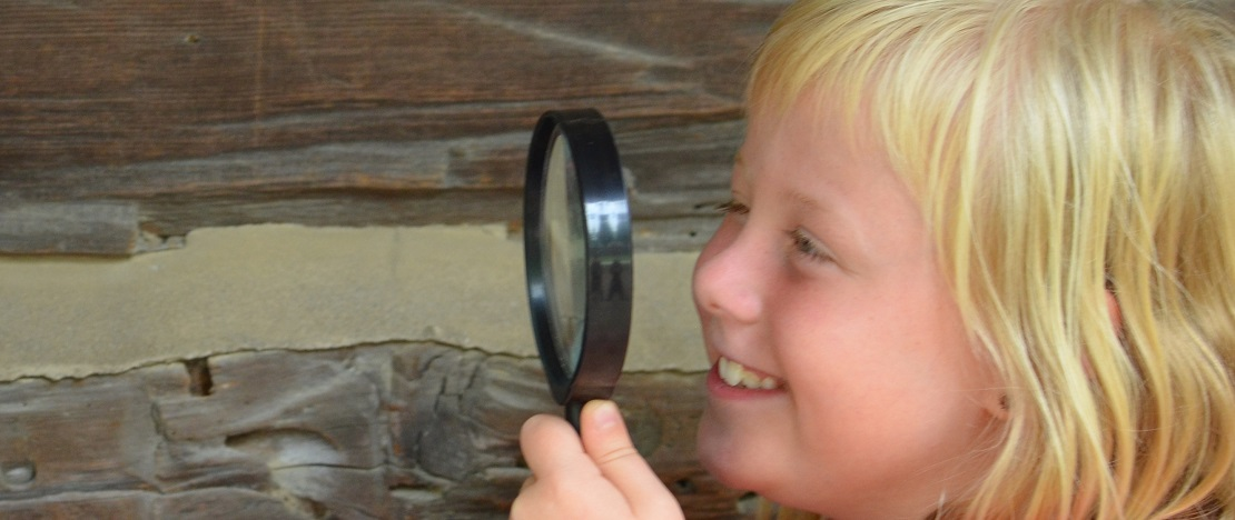 girl with magnifying glass participates in TRCA virtual nature spy camp