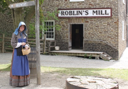 costumed interpreter stands outside Roblins Mill at Black Creek Pioneer Village