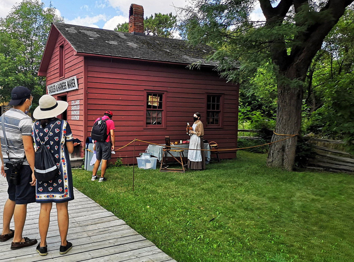 visitors on self-guided tour of Black Creek Pioneer Village stop at Discovery Station next to Harness Makers Shop