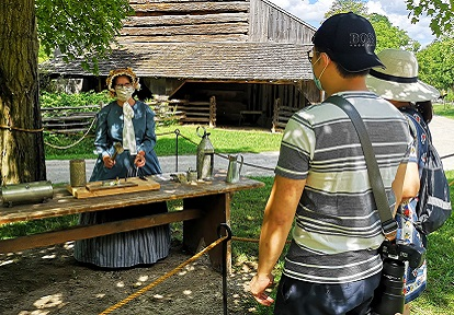 visitors on self-guided tour of Black Creek Pioneer Village observe tinsmithing demonstration