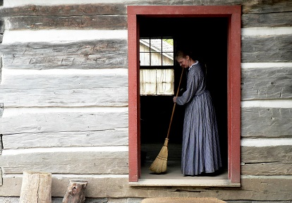 history actor with broom sweeps doorway of first Daniel Stong house at Black Creek Pioneer Village