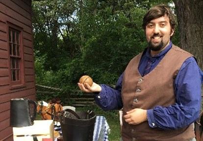 Black Creek Pioneer Village interpreter wearing period costume displays historical artifacts