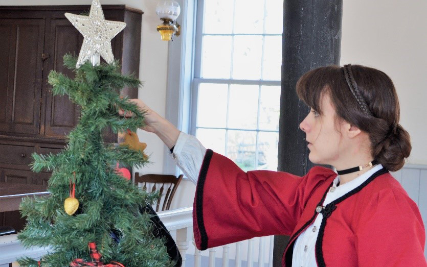history actor in 19th century costume decorates Christmas tree at Black Creek Pioneer Village