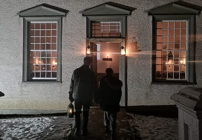couple approaches village meeting house after dark