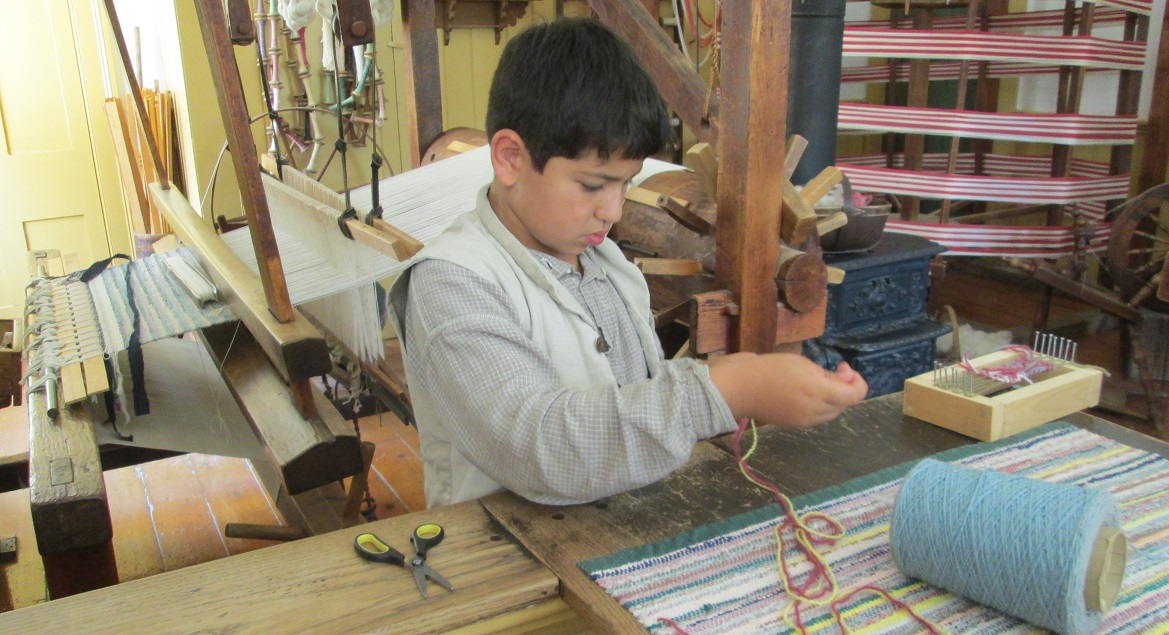 summer camper learns 19th century weaving technique at Black Creek Pioneer Village