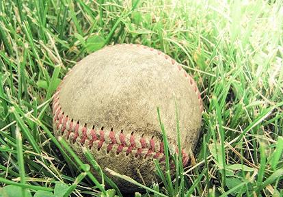 battered baseball lying in the grass
