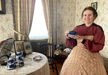 Victorian woman wearing hoop skirt enjoys cup of tea in the parlour