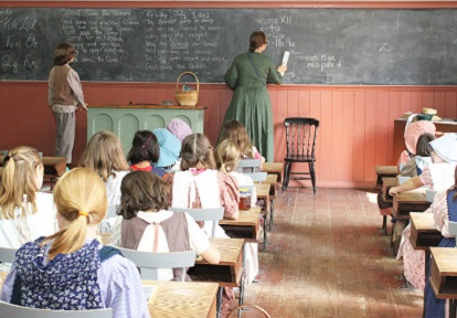 teacher leads class in one-room 19th century rural schoolhouse