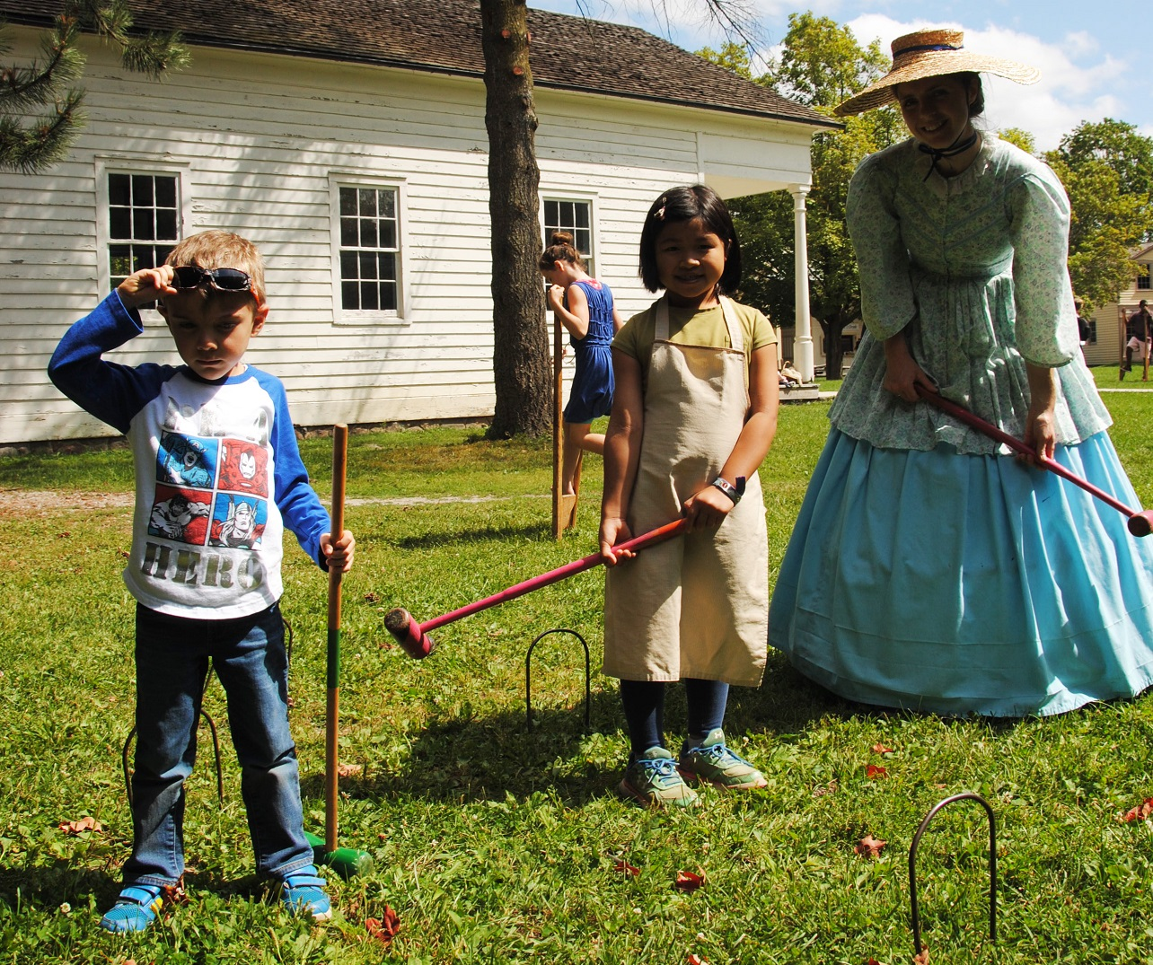 children play croquet with costumed educator on a summer day at Black Creek Pioneer Village