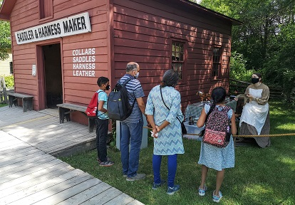 family members enjoy a guided outdoor experience at the saddle and harness making shop at Black Creek Pioneer Village