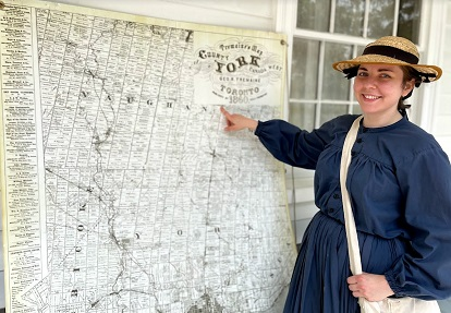 history actor in period costume studies historic map of 19th century Toronto area at Black Creek Pioneer Village