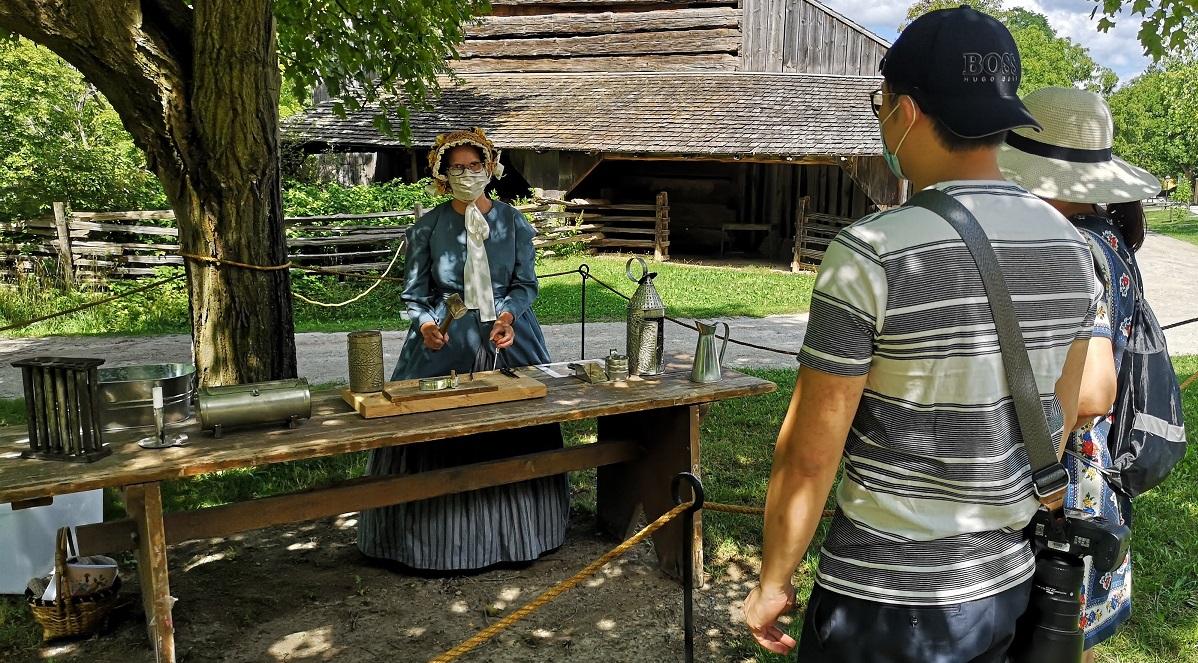 costumed educator wearing mask presents outdoor tinsmithing demonstration at Black Creek Pioneer Village