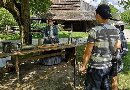 visitors to Black Creek Pioneer Village engage in social distancing while watching presentation by masked costume educator at Black Creek Pioneer Village