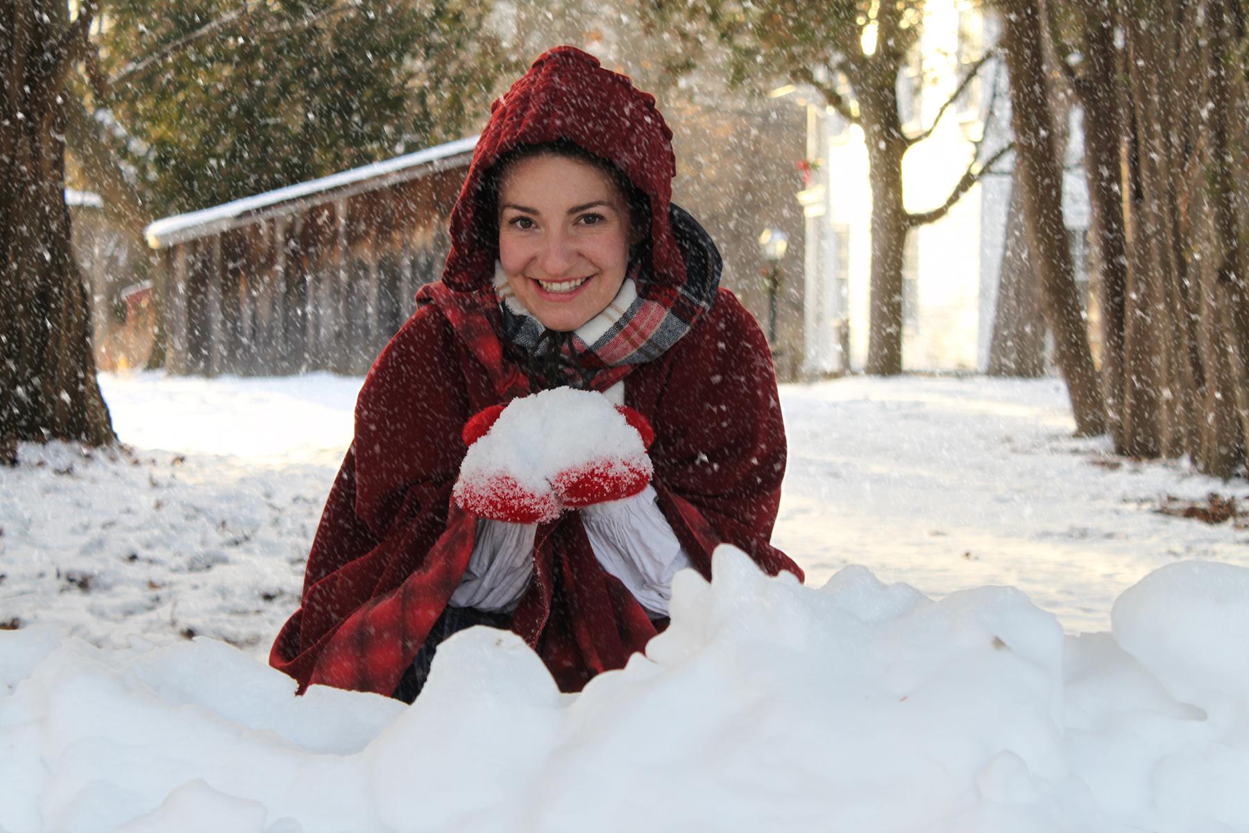 History actor in 19th century costume enjoys winter scene at Black Creek Pioneer Village