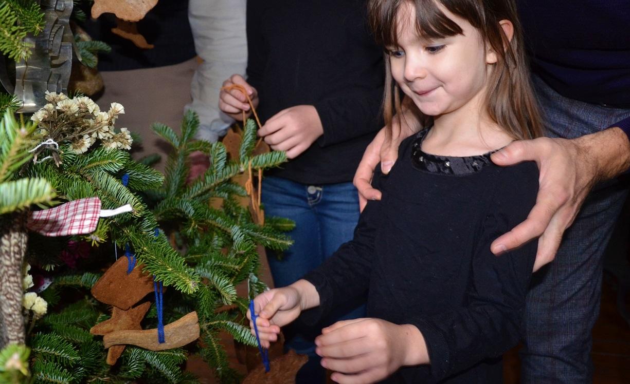 child helps to decorate Christmas tree at Black Creek Pioneer Village