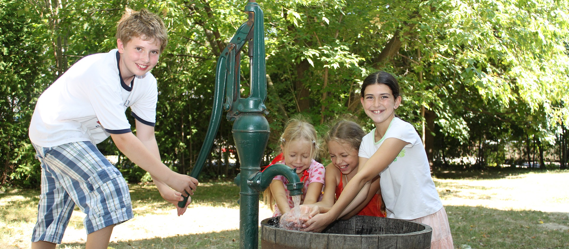 kids operate a water pump at a Black Creek Pioneer Village summer day camp